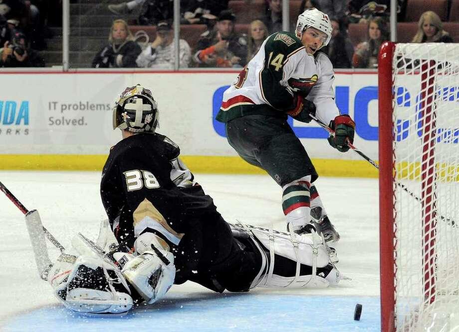 MARK J. TERRILL: ASSOCIATED PRESS HARMLESS: The Wild's Darroll Powe, right, has Ducks goalie Dan Ellis beaten, but the puck rolls through the crease. Photo: Mark J. Terrill / AP