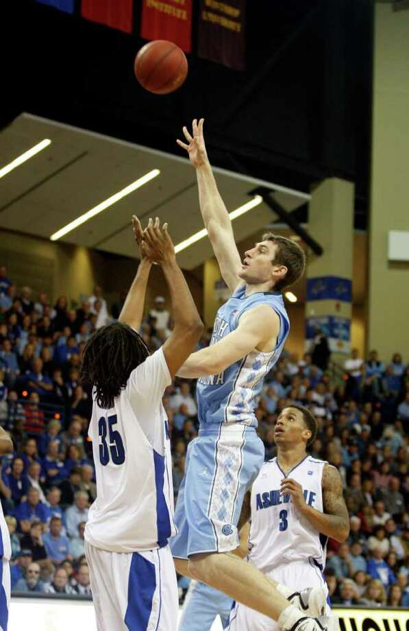 North Carolina center Tyler Zeller, right,shoots over UNC Asheville forward Jon Nwannunu in the second half of an NCAA college basketball game Sunday, Nov. 13, 2011 in Asheville, N.C. Zeller scored 27 points as North Carolina won 91-75. (AP Photo/Nell Redmond) Photo: Nell Redmond