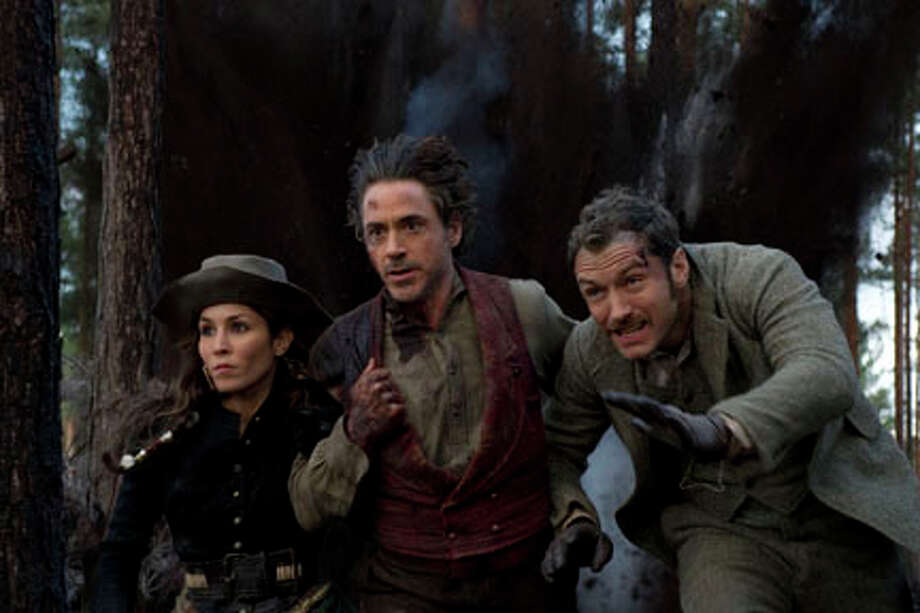 "(L-R) Noomi Rapace as Sim, Robert Downey Jr. as Sherlock Holmes and Jude Law as Dr. Watson in ""Sherlock Holmes: A Game of Shadows."" Photo: Daniel Smith / (C) 2011 WARNER BROS. ENTERTAINMENT INC. - U.S., CANADA, BAHAMAS & BERMUDA (C) 2011 VILLAGE ROADSHOW FILMS (BVI) LIMITED - ALL OTHER TERRITORIES"