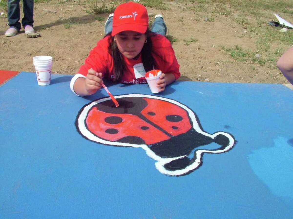Ten-year-old Vanessa Ramon of Forbes Elementary paints a lady bug on the sidewalk at a new playground at Sgt. Matthew E. Mendoza Park.