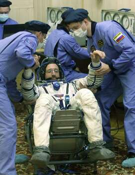 Russian Space Agency experts help International Space Station (ISS) Expedition 30 commander, US astronaut Dan Burbank after inspecting his space suit at the Russian leased Kazakhstan's Baikonur cosmodrome. Photo: MIKHAIL METZEL, Getty / AFP