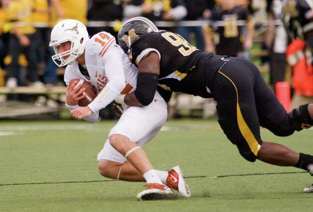 Texas quarterback David Ash (14) is sacked by Missouri's Terrell Resonno, right, during the second quarter of an NCAA college football game Saturday, Nov. 12, 2011, in Columbia, Mo. Photo: AP