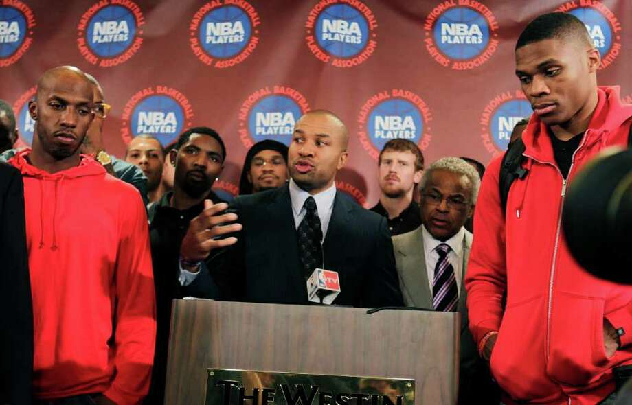 Surrounded by NBA players, including New York Knicks' Chauncy Billups, left, and Oklahoma City Thunder's Russell Westbrook, right, NBA Players Association president Derek Fisher speaks during a news conference after a meeting of the players' union in New York, Monday, Nov. 14, 2011. The NBA players rejected the league's latest offer and have begun the process to disband the union. Photo: AP