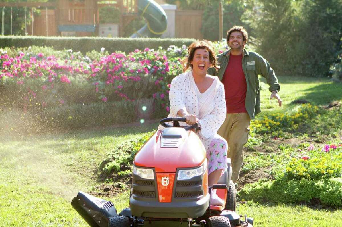 Jill (Adam Sandler) drives the lawnmower around and is out of control as Felipe (Eugenio Derbez) chases her around