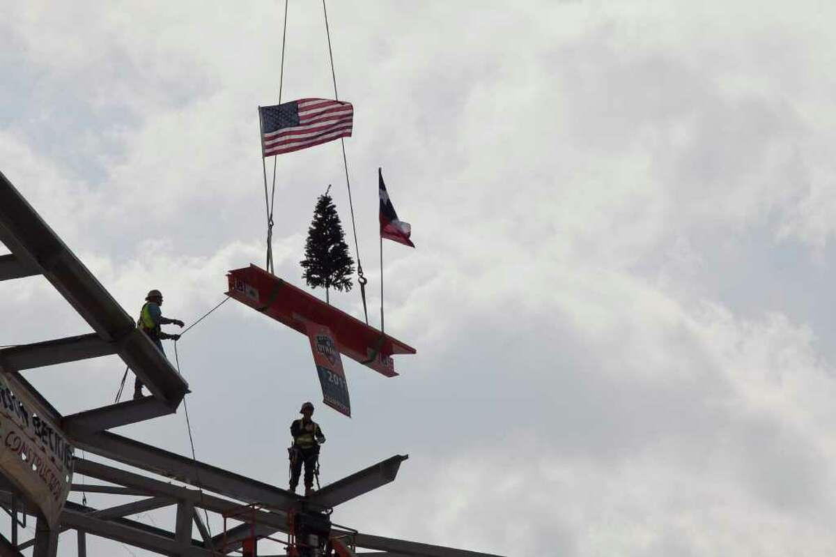 Iron workers Jose Rivera, left, and Noe Rosas install the last steel beam into the Houston Dynamo's new stadium Monday noon November 14, 2011. The installation of the beam is a key moment in the progression toward the opening of the stadium in May. A Christmas tree sitting on the beam is a tradition in the topping out ceremony.