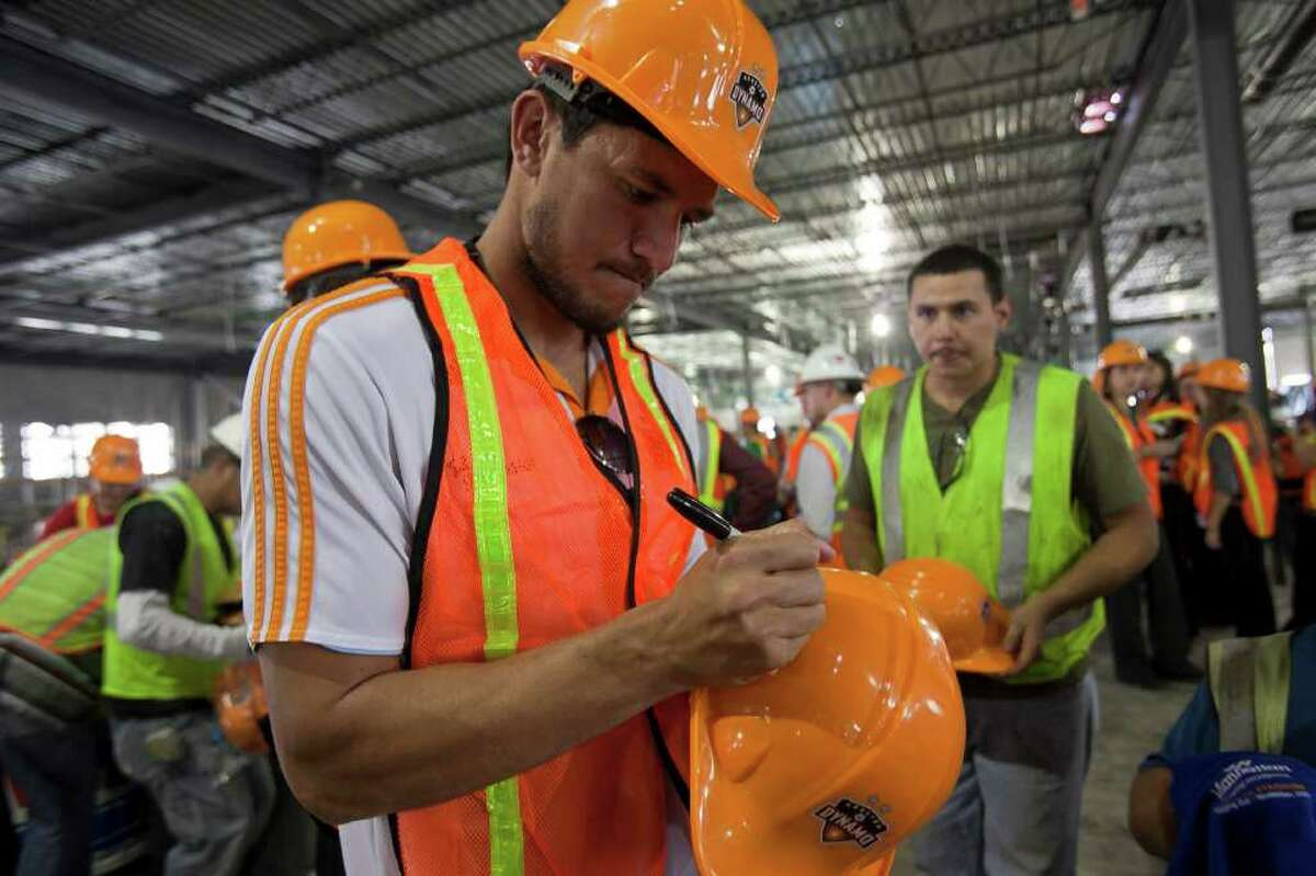 Houston Dynamo star forward Brian Ching signs hard hats for construction workers Monday noon November 14, 2011 after the last steel beam was installed in the soccer team's new stadium.