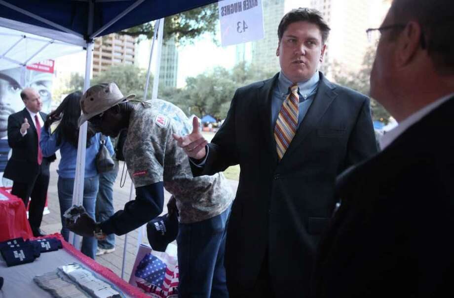 (Center) US Army Veteran Brandon Schumacher speaks to Bill Pricer, representative Baker Hughes, during the AT&T Veterans Day Job Fair outside City Hall on Friday, Nov. 11, 2011.  Approximately 45 booths were set up around the reflection pool where veterans gathered employment information and onsite interviews with company recruiters.  ( Mayra Beltran / Houston Chronicle ) Photo: Mayra Beltran / © 2011 Houston Chronicle