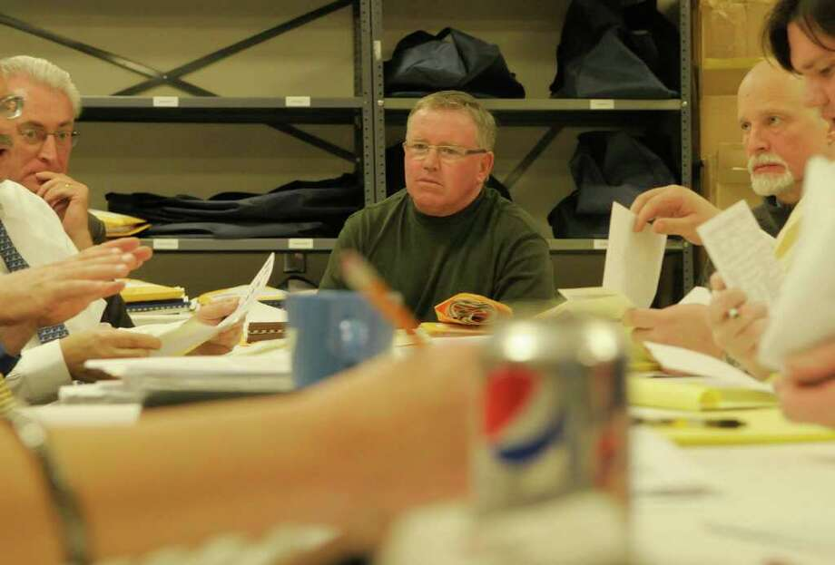 Dean Bodnar, left, Republican incumbent Troy city councilman for district three and Russell Ziemba, far right, the Democrat challenger for the district three seat look on as Rensselaer County Board of Elections Kevin O'Malley, center and other workers count absentee ballots on Monday, Nov. 14, 2011 at the Rensselaer County Board of Elections in Troy.  (Paul Buckowski / Times Union) Photo: Paul Buckowski / 00015389A