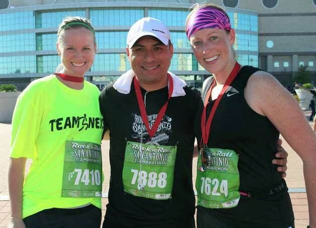 FEATURES; ACS RNR MARATHON JMS; 11/13/11; From the left, Susan Tourk, Andrew Mora and Sadie Cambon after finishing the Rock 'n' Roll Marathon, Sunday, November 13, 2011, at The Alamodome in San Antonio. ( Photo by J. Michael Short / SPECIAL ) Photo: J. MICHAEL SHORT, SPECIAL TO THE EXPRESS-NEWS / THE SAN ANTONIO EXPRESS-NEWS