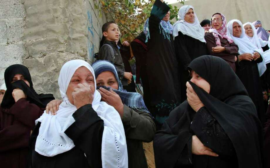 Palestinian relatives of Mohammed Al Kelani, a Hamas security officer, weep during his funeral in Beit Lahiya, northern Gaza Strip, Monday, Nov. 14, 2011. Al Kelani was killed during an Israeli air strike while he was at Hamas Navel police building early Monday. (AP Photo/Adel Hana) Photo: Adel Hana / AP