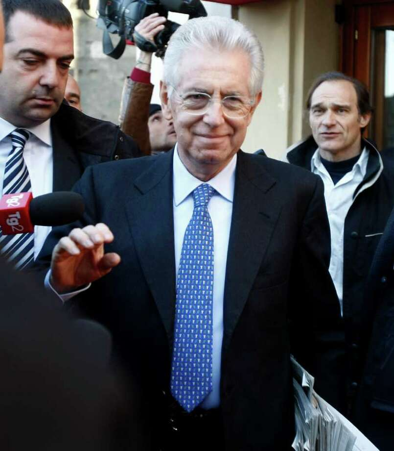 Italy's new premier-designate economist Mario Monti leaves the hotel to start talks with parties' representatives in Rome, Monday, Nov. 14, 2011. Italian borrowing costs are well below dangerous levels Monday, as markets express confidence in the prospect that leading economist Mario Monti will form a new government without politicians. Italian president Giorgio Napolitano tapped Monti on Sunday to create a government of experts to implement structural economic reforms aimed at bringing down Italy's stubbornly high public debt. (AP Photo/Pier Paolo Cito) Photo: Pier Paolo Cito / AP