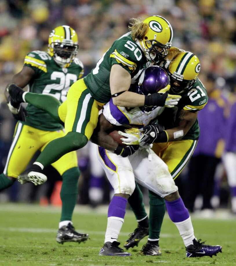 MORRY GASH: ASSOCIATED PRESS YO, ADRIAN: Green Bay defenders A.J. Hawk (50) and Charles Woodson (21) put the clamps on Minnesota's Adrian Peterson, stopping him for a loss in the second half. Photo: Morry Gash / AP