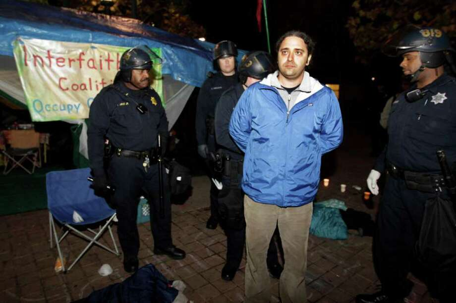 Police hold a demonstrator at an encampment for the Occupy Wall Street movement in Oakland, Calif., Monday, Nov. 14, 2011. Police in Oakland began clearing out a weeks-old encampment early Monday after issuing several warnings to Occupy demonstrators. (AP Photo/Paul Sakuma) Photo: Paul Sakuma