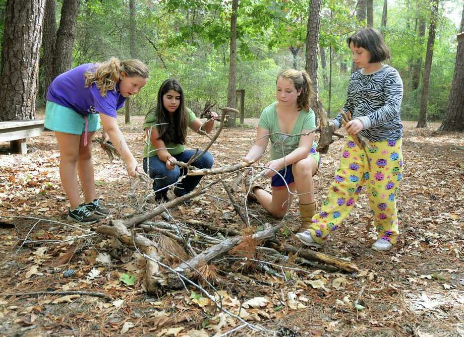 DAVID HOPPER: FOR THE CHRONICLE BURN BAN: Spring Branch Girl Scouts Kaeli Adams, Gabriella Ramirez, Riley Fairchild, and Rachel Thompson stack wood for a campfire, even though they won't be able to have a fire, during their camping trip at Camp Agnes Arnold in Conroe. Photo: David Hopper / freelance