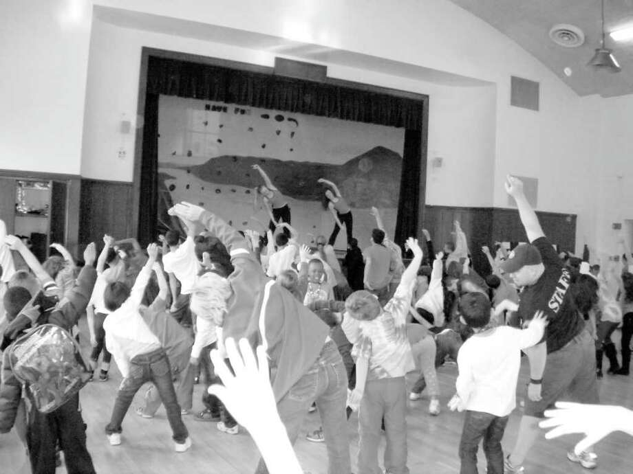 """All together now STRETCH!!"" said Marisa Hann while leading 98 children and adults in a Zumba kickoff event at the Boys and Girls Club of Greenwich on Election Day. Hann, an Ambassador-level Girl Scout is working on her Gold Award teaching Zumba and nutrition. Assisting Hann on stage with dance moves and to get the party going was Caroline Pluta. Both are members of the Greenwich High School Varsity Dance Team. Photo: Contributed Photo"