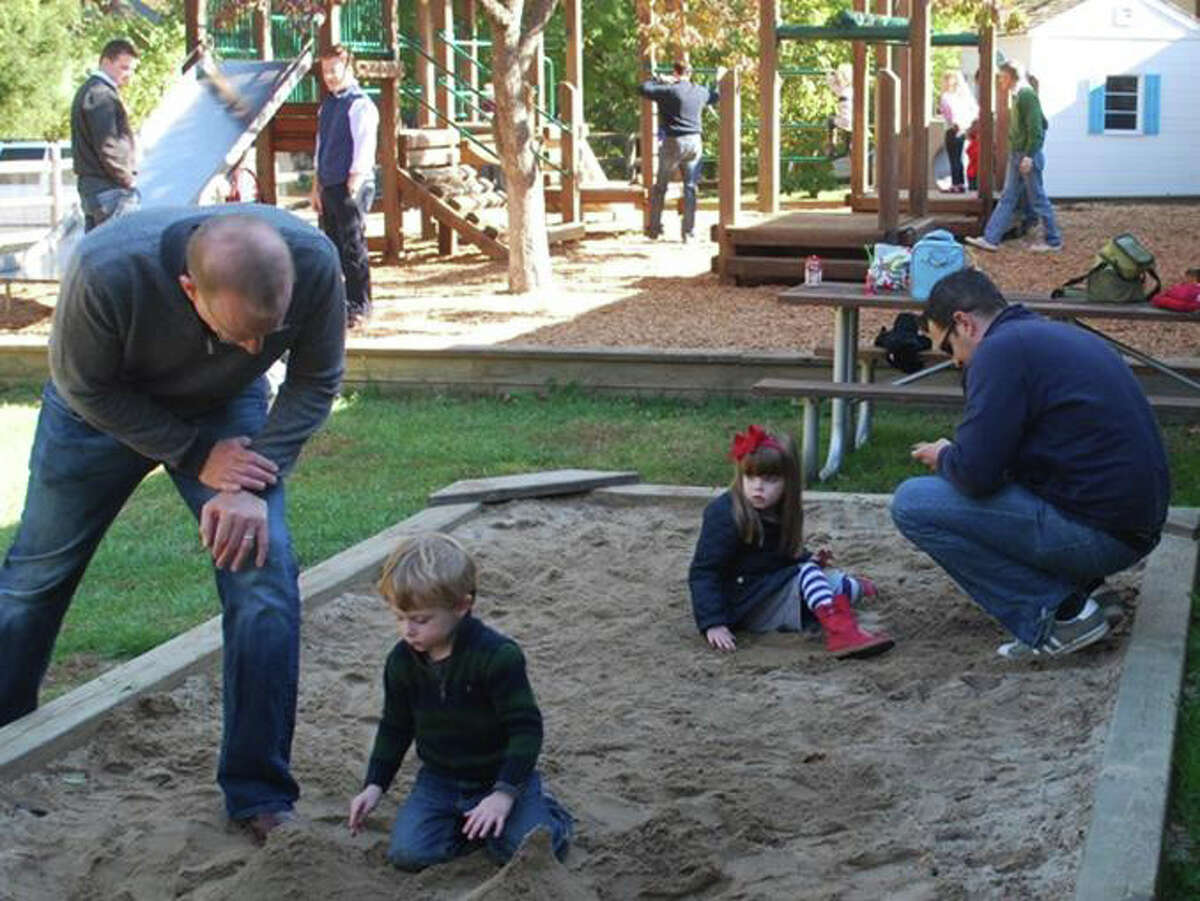 In the sandbox, from left, Jackson Demko with his dad Micheal and Annabelle Bristol with her dad Christopher.