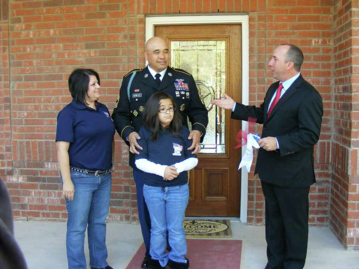 John Gonsalves, president and founder of Homes For Our Troops, on welcomes retired U.S. Army Master Sgt. Daniel Robles, his wife, Ernestine, and their daughter, Mary, to their new home in the Georg Ranch subdivision in Garden Ridge.