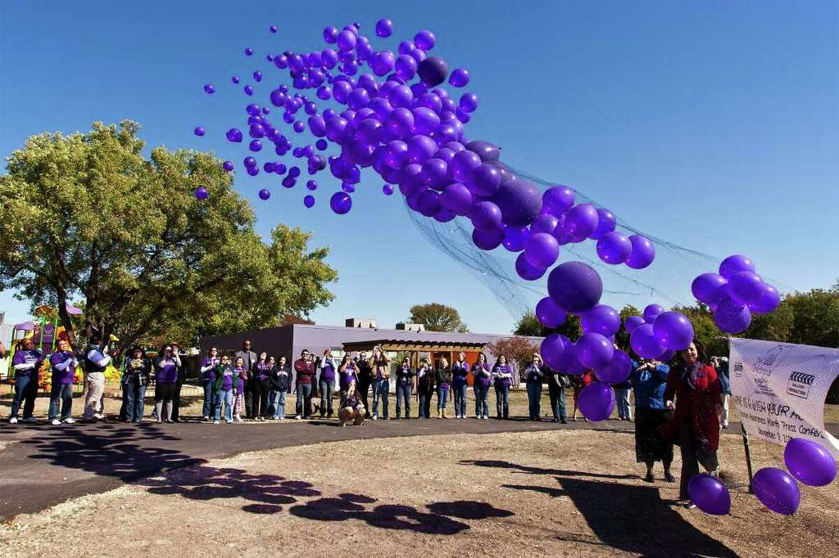 Bystanders applaud as 532 purple balloons, representing the 532 children eligible for adoption in San Antonio, are released Friday from The Children's Shelter.