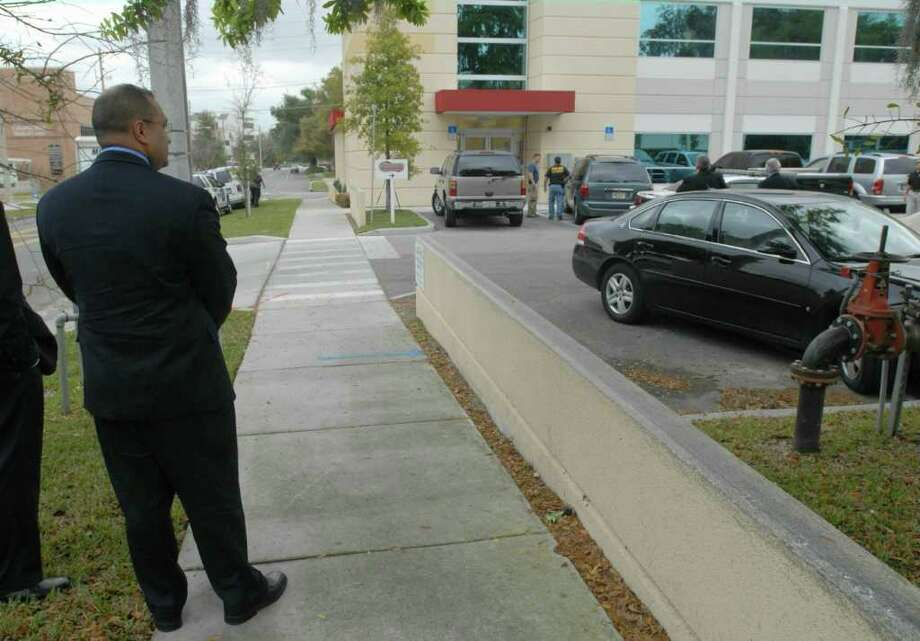 "Albany County District Attorney David Soares waits on a sidewalk near Signature Compounding Pharmacy in Orlando during a police raid there on Feb. 27, 2007. The investigation probed a maze of shadowy pharmacies and Web-based ""clinics"" that reaped millions of dollars in profit by allegedly exploiting federal and state prescription laws, according to court records. Criminal charges against the pharmacy's former operators remain pending in Albany. (Paul Buckowski / Times Union) Photo: Paul Buckowski / Albany Times  Union"