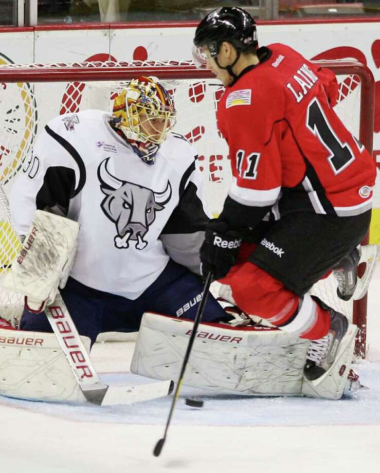 Abbotsford Heat's Quintin Laing, right, jumps to avoid the puck as it slides under San Antonio Rampage goaltender Jacob Markstrom for an Abbotsford goal during the second period of an AHL hockey game, Tuesday, Nov. 15, 2011, in San Antonio. Photo: Darren Abate, Darren Abate/pressphotointl.com / Darren Abate/pressphotointl.com