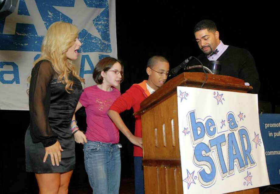 WWE Diva Natalya and WWE Superstar David Otunga look on as 7th grade students Maya Todrin and Branden Lee of Turn of River Middle School in Stamford, Conn. take turns reading a pledge to not bully on Tuesday November 15, 2011. Photo: Dru Nadler / Stamford Advocate Freelance