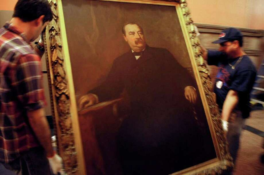 A painting of Grover Cleveland is placed onto a cart as workers from the State Museum and OGS removed the paintings of past governors from the walls in the Hall of Governors on the second floor of the capitol on Tuesday, Nov. 15, 2011.  (Paul Buckowski / Times Union) Photo: Paul Buckowski / 00015409A