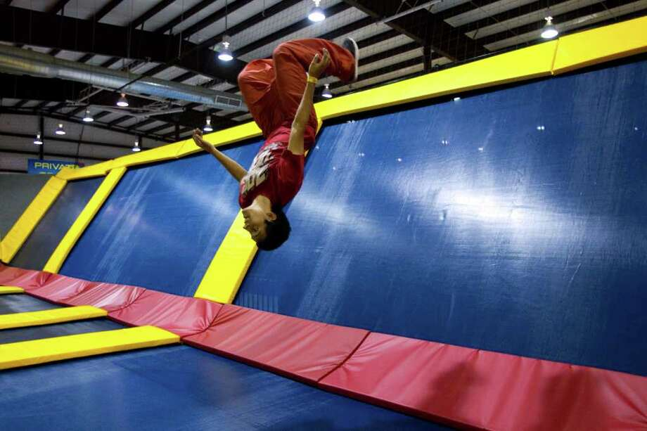 BRETT COOMER : STAFF  UPSIDE DOWN: Joshua Rodriguez, 20, does a back flip while bouncing on trampolines at Sky High Sports, a newly opened trampoline recreation center in west Houston. Photo: Brett Coomer / © 2011 Houston Chronicle