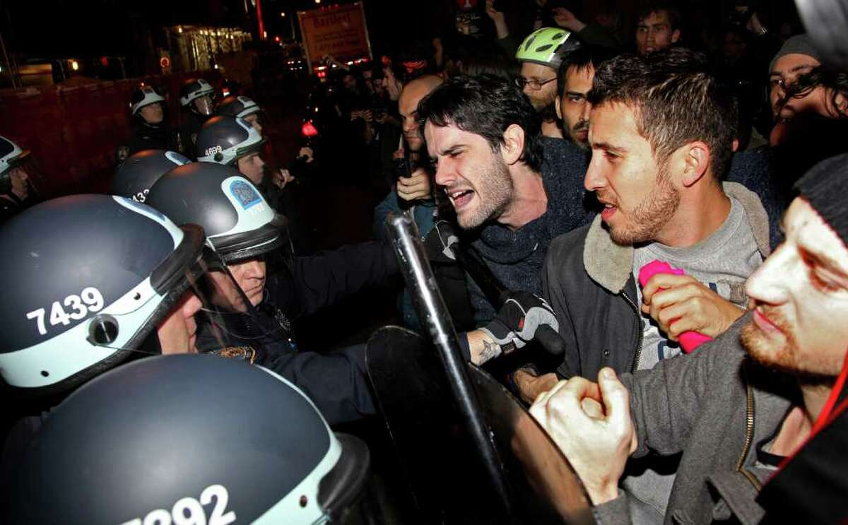 Occupy Wall Street protesters clash with police at Zuccotti Park after being ordered to leave their longtime encampment in New York, early Tuesday, Nov. 15, 2011. At about 1 a.m. Tuesday, police handed out notices from the park's owner, Brookfield Office Properties, and the city saying that the park had to be cleared because it had become unsanitary and hazardous. Protesters were told they could return, but without sleeping bags, tarps or tents.