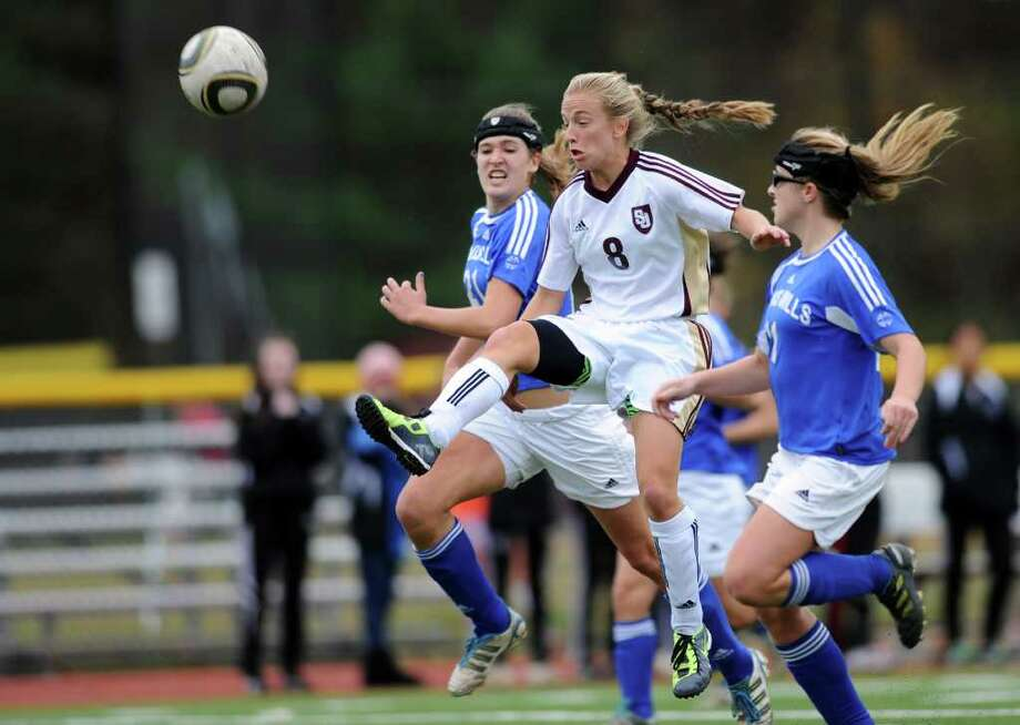 St. Joseph's Samantha Grasso takes a shot between Lewis Mills defenders, Lesleigh Carter, left, and Alison Hannon, right, during the Class M girls soccer  quarterfinal match Tuesday, Nov. 15, 2011 at St. Joseph High School in Trumbull, Conn. Photo: Autumn Driscoll / Connecticut Post