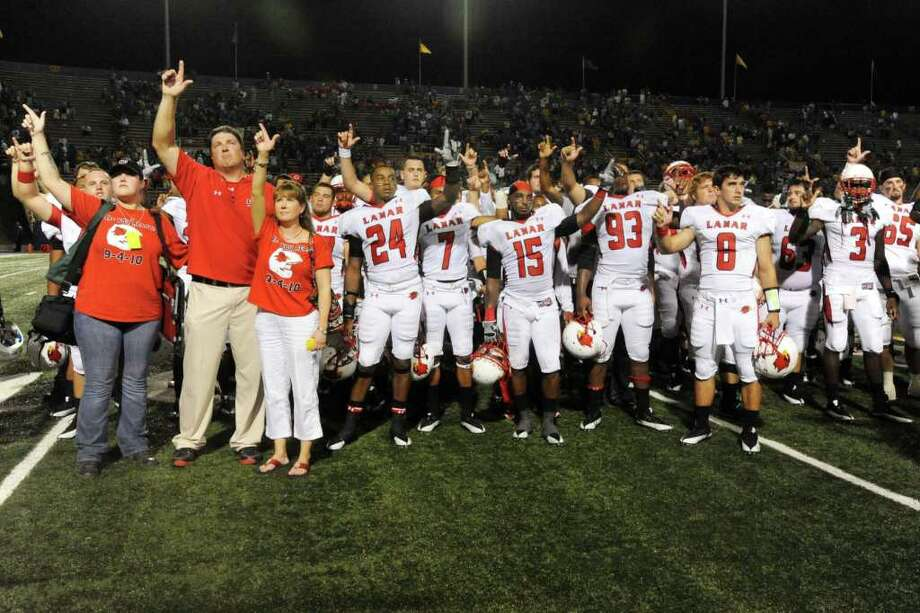 Lamar head coach Ray Woodard, left, stands with his family and players for the Lamar school song after the Cardinals 30-27 loss against McNeese State at Cowboy Stadium in Lake Charles La. on Saturday, September 4, 2010  Valentino Mauricio/The Enterprise Photo: Valentino Mauricio / Beaumont