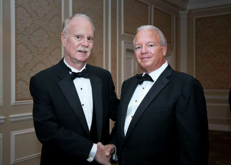 Dr. Dickerman Hollister, left, recipient of the 2011 President's Award, gets a congratulatory handshake from Frank Corvino, president and chief executive officer of Greenwich Hospital, at the recent Casablanca Gala for Greenwich Hospital. Photo: Elaine Ubina/Contributed Photo / Greenwich Citizen