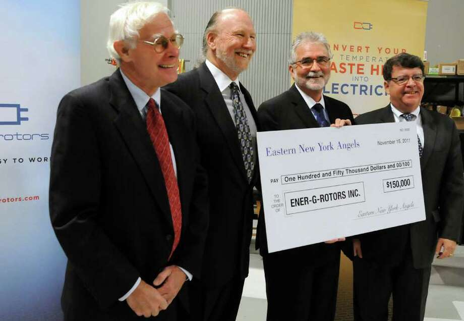 Joseph Richardson, left, and Richard Frederick, second from left, both founders of Eastern New York Angels, present a check to Michael Newell, CEO of Ener-G-Roters, center, with F. Michael Tucker of the Center for Economic Growth, during a news conference on Tuesday, Nov. 15, 2011, at Ener-G-Rotors in Rotterdam, N.Y. (Cindy Schultz / Times Union) Photo: Cindy Schultz / 00015407A