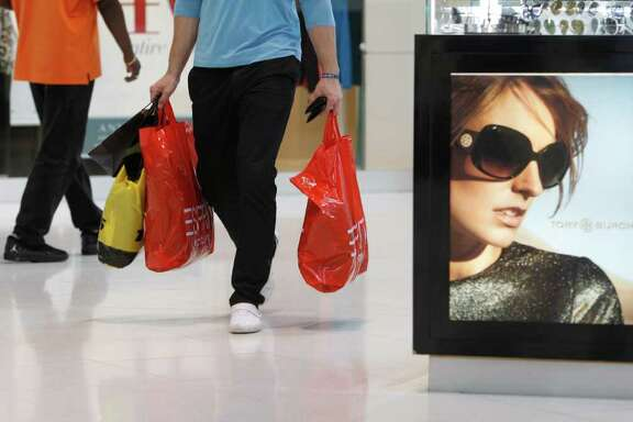 In this Nov. 9, 2011 photo, a shopper carries purchases while shopping at Dolphin Mall, in Miami. Americans spent more on autos, electronics and building supplies in October, pushing retail sales up for a fifth straight month. (AP Photo/Lynne Sladky)