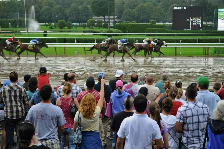 Race fans cheer on horses as they head to the finish line of the 5th race on the last day of racing for the year at Saratoga Race Course on Monday Sept. 5, 2011 in Saratoga Springs, NY.  (Philip Kamrass / Times Union) Photo: Philip Kamrass / 00014511A