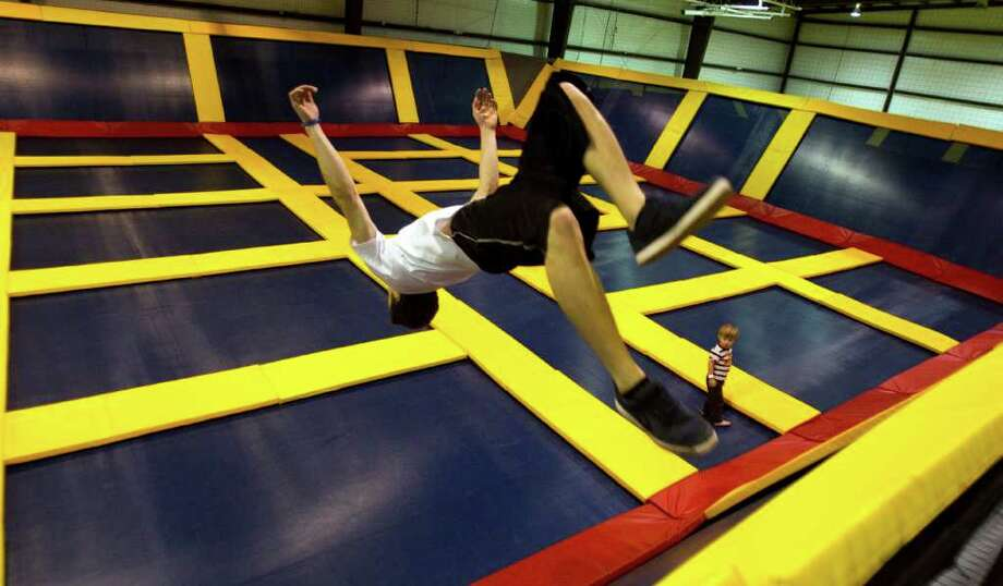 Alex Lippke, 20, does a back flip as he bounces off a side trampoline at Sky High Sports in Houston. Sky High Sports is a newly-opened trampoline recreation center in west Houston. Photo: Brett Coomer, Houston Chronicle / © 2011 Houston Chronicle