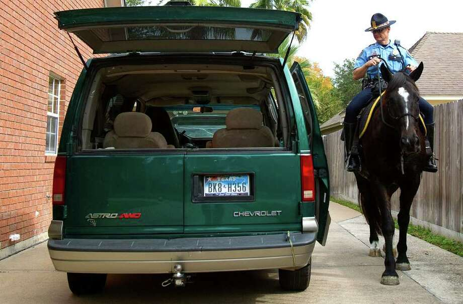 Houston Police mounted patrol office Randall Wallace looks at an open van with his horse, Jeremiah, as he makes his way through through Bay Oaks as part of an effort to cut down the burglaries in Clear Lake. The three-day initiative is designed to visibly increase HPD's presence in three different neighborhoods experiencing a rise in home burglaries. Photo: Cody Duty, Houston Chronicle / © 2011 Houston Chronicle
