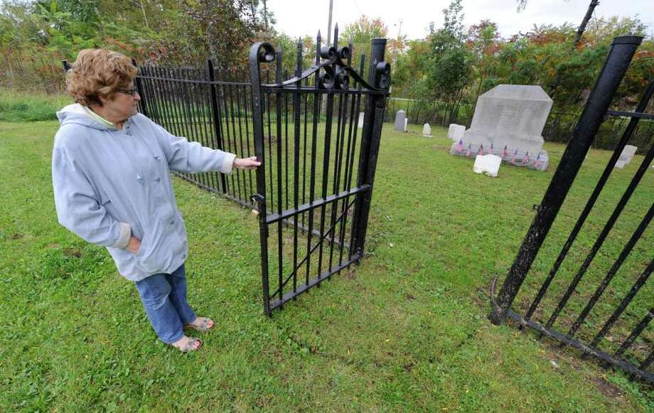 Johanna Shogan, of the Daughter of the American Revolution, opens the gate to the VanSchaick Cemetery in Cohoes.  (Skip Dickstein/Times Union) Photo: Skip Dickstein / 2011