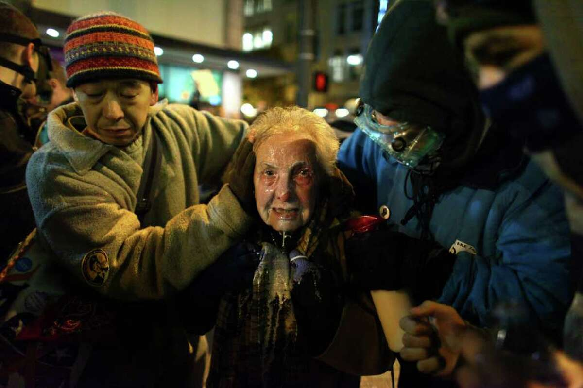 Seattle activist Dorli Rainey, 84, reacts after being hit with pepper spray during an Occupy Seattle protest on Tuesday, November 15, 2011 at Westlake Park. Protesters gathered in the intersection of 5th Avenue and Pine Street after marching from their camp at Seattle Central Community College in support of Occupy Wall Street. Many refused to move from the intersection after being ordered by police. Police then began spraying pepper spray into the gathered crowd, hitting dozens of people. A pregnant woman was taken from the melee in an ambulance after being struck with spray.