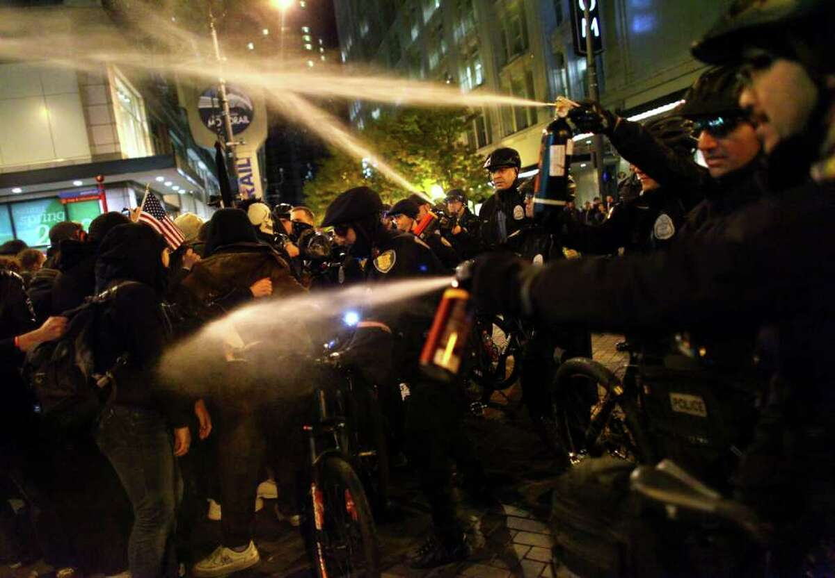 Seattle Police officers deploy pepper spray into a crowd during an Occupy Seattle protest on Tuesday, November 15, 2011 at Westlake Park. Protesters gathered in the intersection of 5th Avenue and Pine Street after marching from their camp at Seattle Central Community College in support of Occupy Wall Street. Many refused to move from the intersection after being ordered by police. Police then began spraying into the gathered crowd hitting dozens of people. A pregnant woman was taken from the melee in an ambulance after being struck with spray. An 84 year-old activist was also hit with spray.