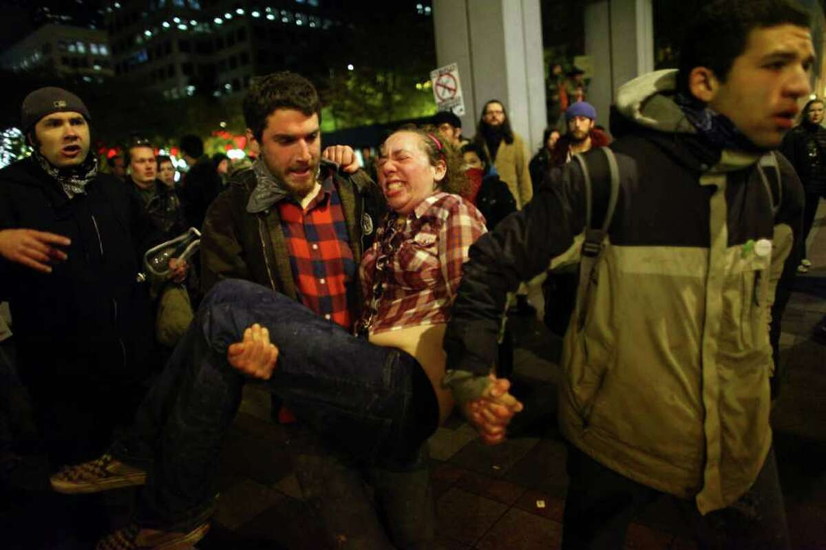 A woman who gave her name as Jennifer and said she was two months pregnant is rushed to an ambulance after being hit with pepper spray at an Occupy Seattle protest on Tuesday, November 15, 2011 at Westlake Park. Protesters gathered in the intersection of 5th Avenue and Pine Street after marching from their camp at Seattle Central Community College in support of Occupy Wall Street. Many refused to move from the intersection after being ordered by police. Police then began spraying into the gathered crowd hitting dozens of people. An 84 year-old activist was also hit with spray.