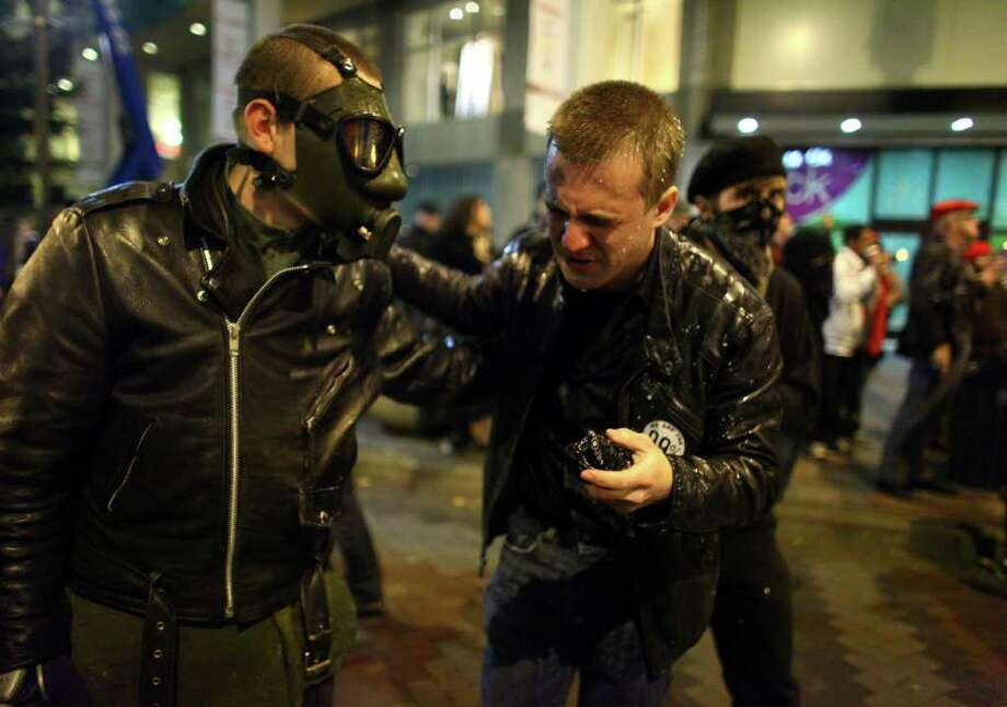 Protesters react after Seattle Police officers deployed pepper spray into a crowd during an Occupy Seattle protest on Tuesday, November 15, 2011 at Westlake Park. Protesters gathered in the intersection of 5th Avenue and Pine Street after marching from their camp at Seattle Central Community College in support of Occupy Wall Street. Many refused to move from the intersection after being ordered by police. Police then began spraying into the gathered crowd hitting dozens of people.  Photo: JOSHUA TRUJILLO / SEATTLEPI.COM