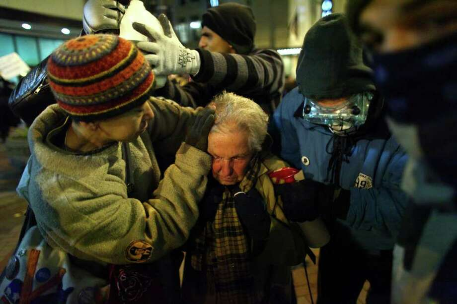 Seattle activist Dorli Rainey, 84, reacts after being hit with pepper spray during an Occupy Seattle protest on Tuesday, November 15, 2011 at Westlake Park.  Photo: JOSHUA TRUJILLO / SEATTLEPI.COM