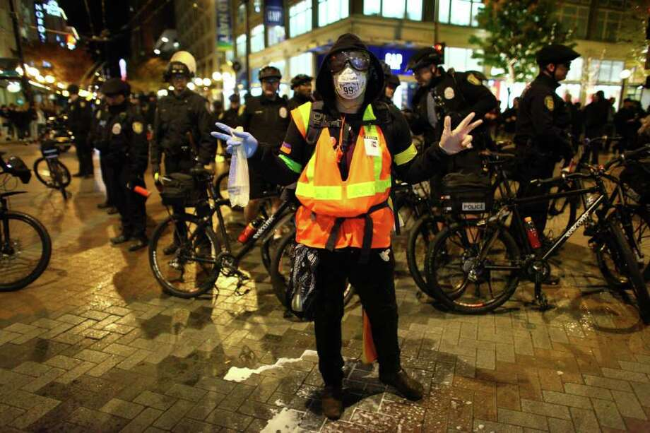 A protester stands in front of Seattle Police during an Occupy Seattle protest on Tuesday, November 15, 2011 at Westlake Park.  Photo: JOSHUA TRUJILLO / SEATTLEPI.COM