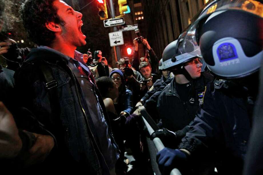 An Occupy Wall Street protester yells out at police after being ordered to leave Zuccotti Park, their longtime encampment in New York, early Tuesday, Nov. 15, 2011. At about 1 a.m. Tuesday, police handed out notices from the park's owner, Brookfield Office Properties, and the city saying that the park had to be cleared because it had become unsanitary and hazardous. Protesters were told they could return, but without sleeping bags, tarps or tents. (AP Photo/Mary Altaffer) Photo: Mary Altaffer