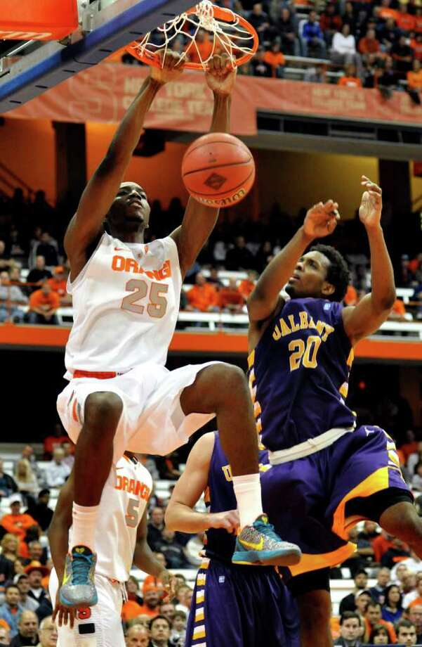Syracuse's Rakeem Christmas dunks against Albany's Gerardo Suero during the second half of the NIT Season Tip-Off NCAA college basketball game in Syracuse, N.Y., Tuesday, Nov. 15, 2011. Syracuse won 98-74. (AP Photo/Kevin Rivoli) Photo: Kevin Rivoli