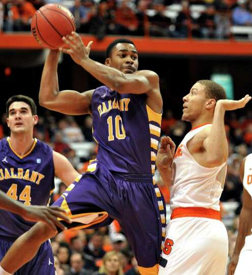 Albany's Mike Black looks to pass as Syracuse's Brandon Triche, right, defends during the first half