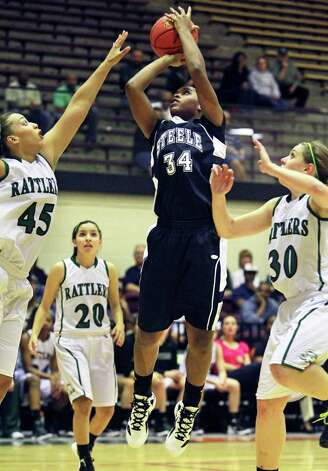 SPORTS   Steele's Erika Chapman splits Corrigan Tibbs (45) and Malorie Dyer for a jumper as Reagan plays Steele in girls basketball at Littleton Gym on November 15, 2011.  Tom Reel/Staff Photo: TOM REEL, SAN ANTONIO EXPRESS-NEWS / © 2011 San Antonio Express-News