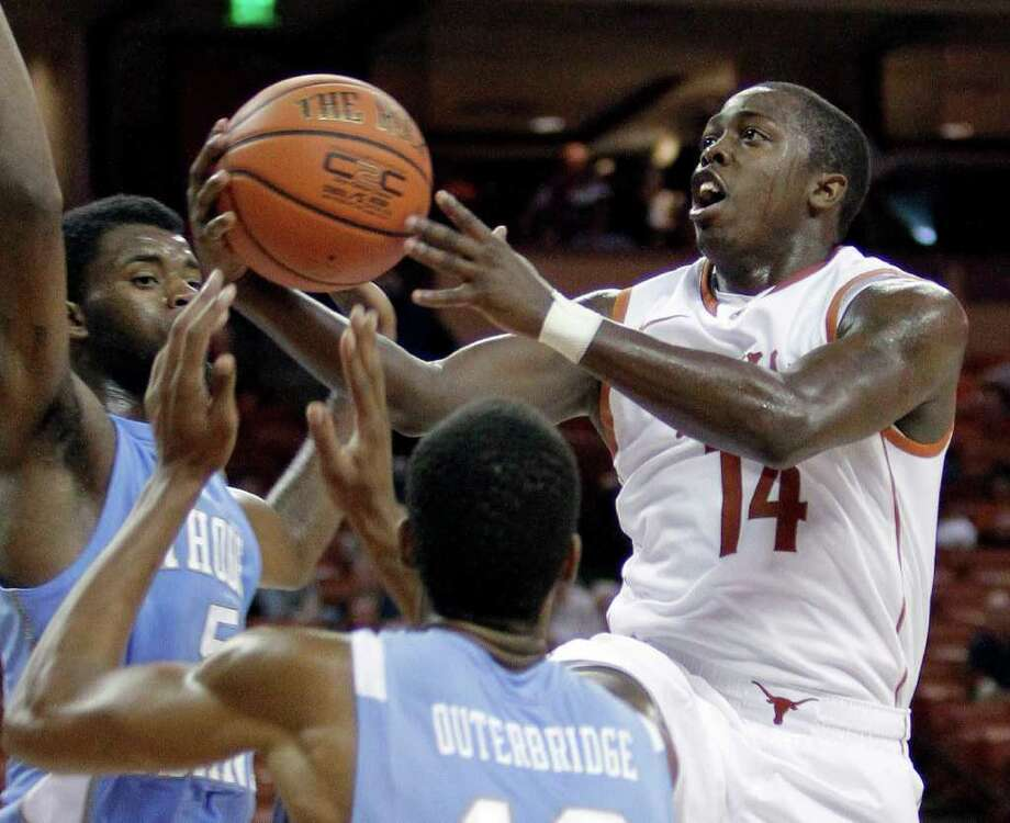 Texas' J'Covan Brown (14) drives to the basket as Rhode Island's Dominique McKoy, left, and Orion Outerbridge defend during the second half of an NCAA college basketball game Tuesday, Nov. 15, 2011, in Austin, Texas. Texas won 100-90. (AP Photo/Eric Gay) Photo: Eric Gay, Associated Press / AP
