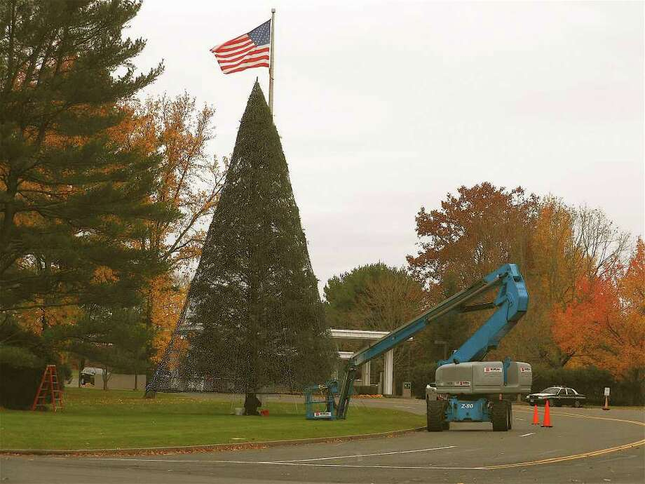 Tuesday's balmy weather sure did not make it feel like it nearly 'tis the Christmas season, but workers at the General Electrtic corporate headquarters on Easton Turnpike were already decorating the Christmas tree out front. Photo: Mike Lauterborn / Fairfield Citizen contributed