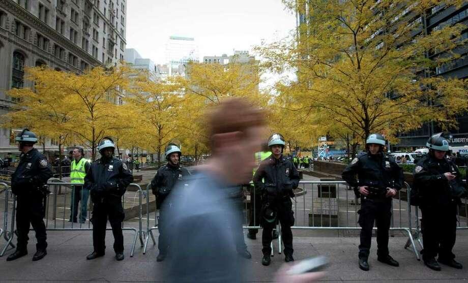 Un peatón camina frente a los agentes de policía de Nueva York que vigilan el parque Zucotti, donde desalojaron a los manifestantes del grupo Occupy Wall Street. Photo: Scott Eells / © 2011 Bloomberg Finance LP